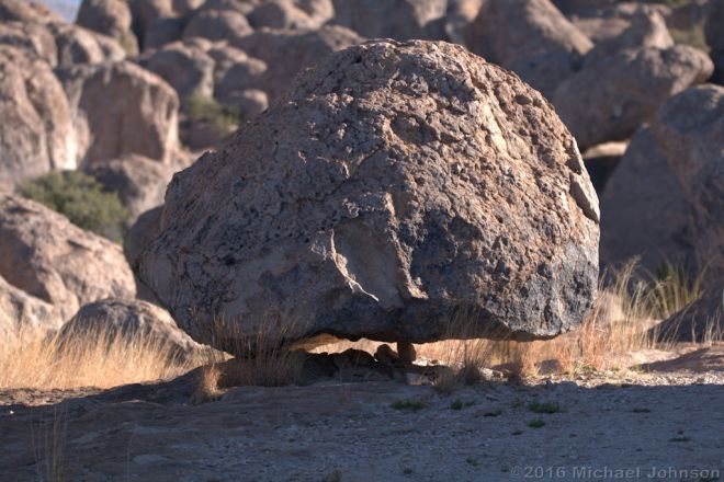 A pretty decent sized boulder being held up by a small rock.